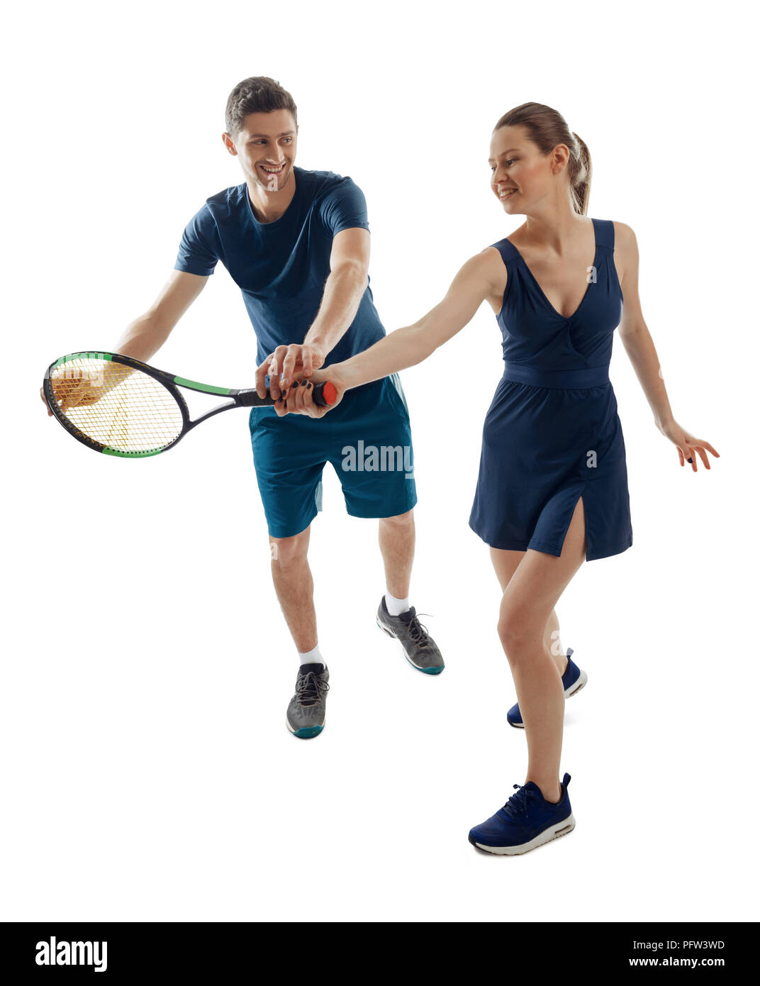 Young woman learning tennis fundamentals with handsome coach. Exploring new and having fun. Sport and leisure. - Stock Image