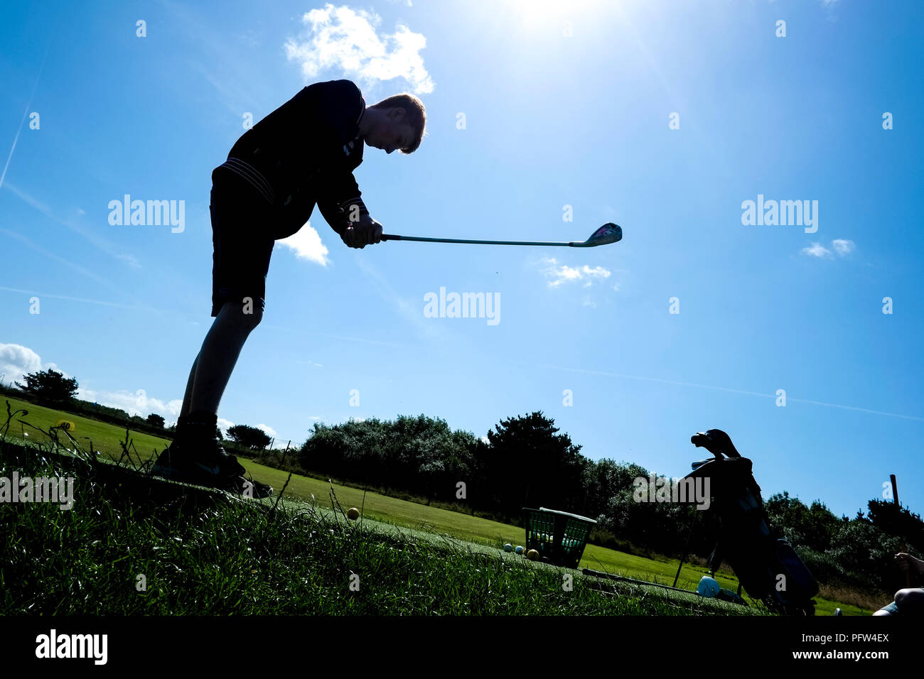 Young teenager taking a swing at a golf ball for the first time. - Stock Image