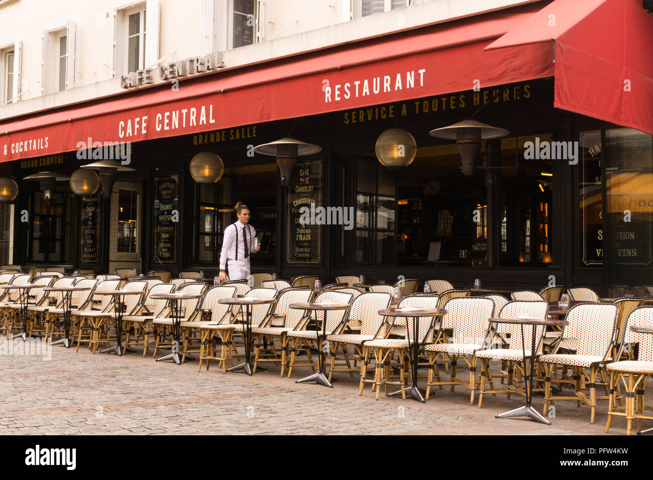 Waiter sets the tables at the Cafe Central restaurant on Rue Cler in Paris, France. - Stock Image