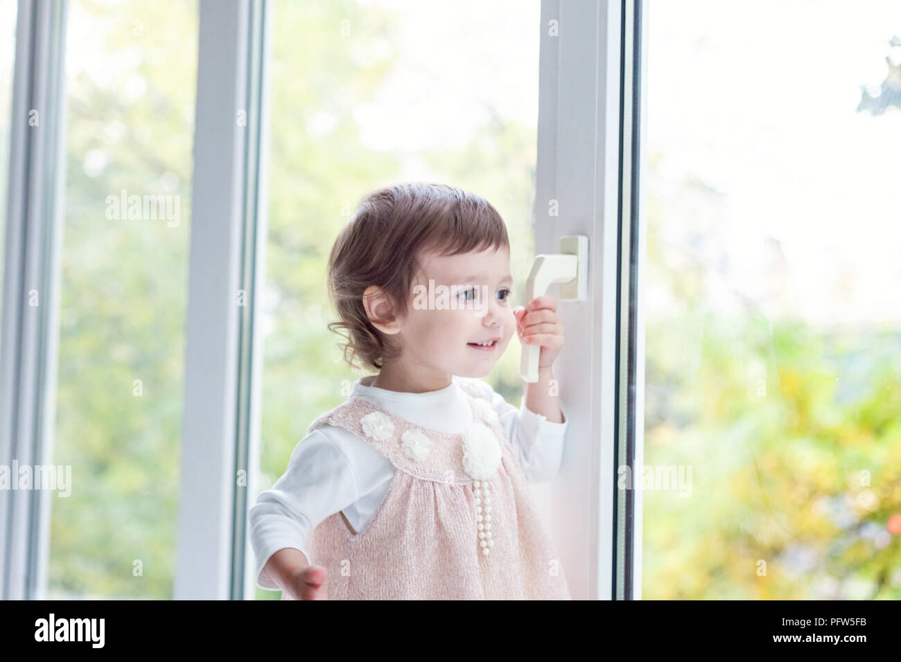 Cute Smiling Baby Girl Standing At Home Near Window Stock Photo