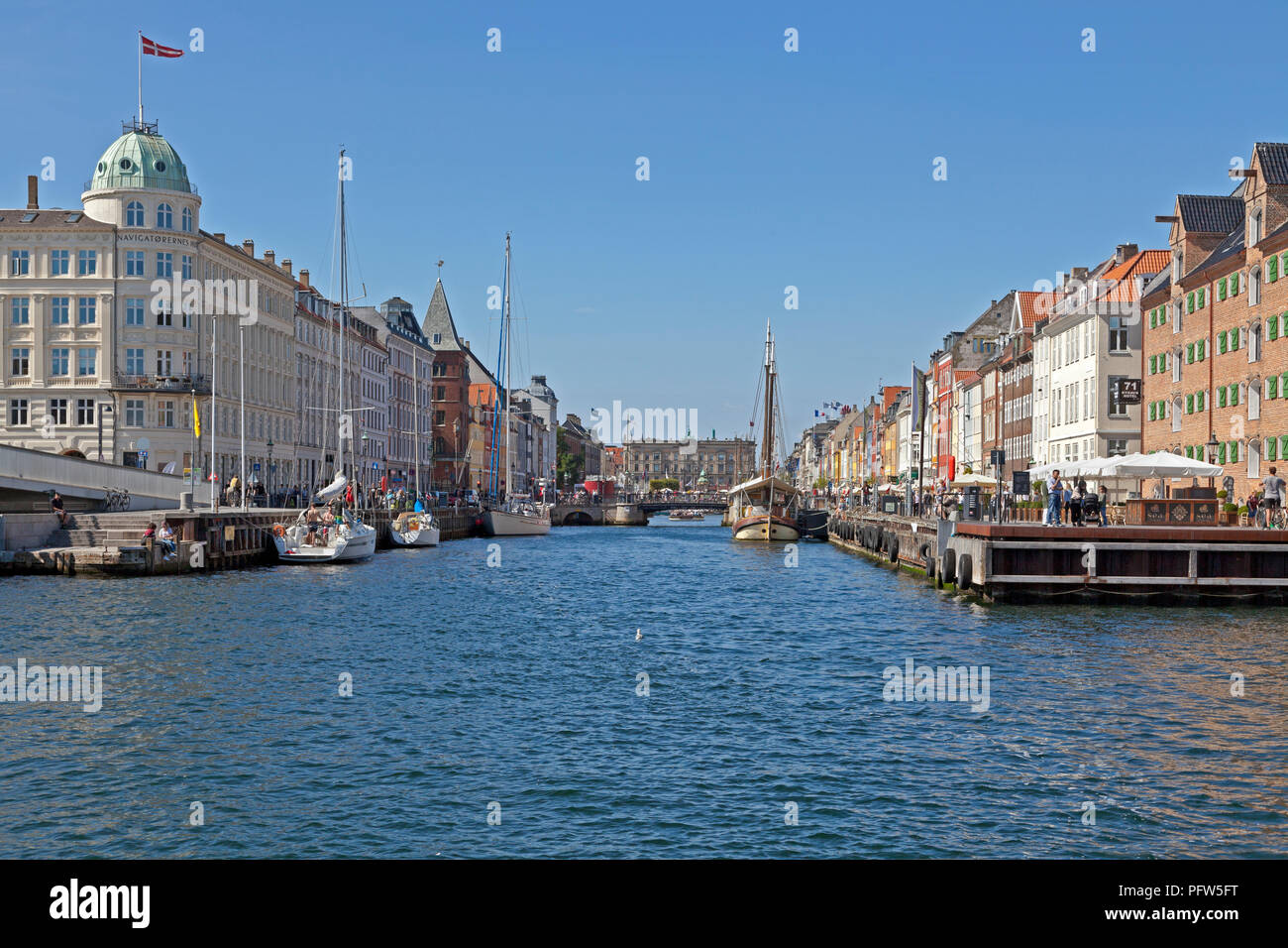 View through Nyhavn canal with vintage ships and colourful houses towards Kongens Nytorv in Copenhagen. Crowded bars and restaurants and vintage ships Stock Photo