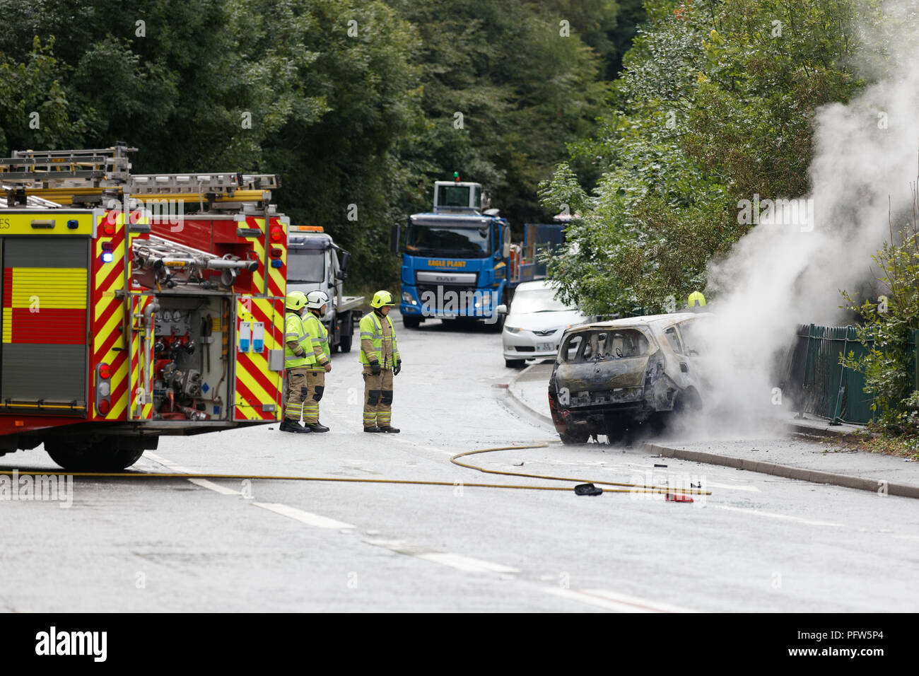 Fire service personnel attend a fire of a red Renault car  in Crumlin, south Wales, UK - Stock Image