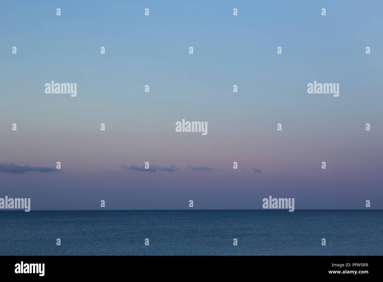 The Kattegat sea stretching to the horizon, with a sky colored violet and blue at dusk. - Stock Image