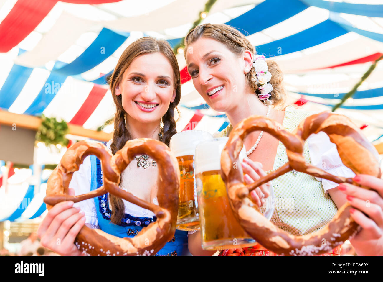 Friends at Bavarian Fair with giant pretzels - Stock Image