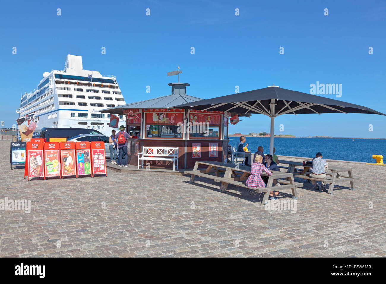 Ice and refreshment stall on the Langelinie pier in the harbour of Copenhagen in late summer. Cruise ship NAUTICA moored at the Langelinie quay. Stock Photo