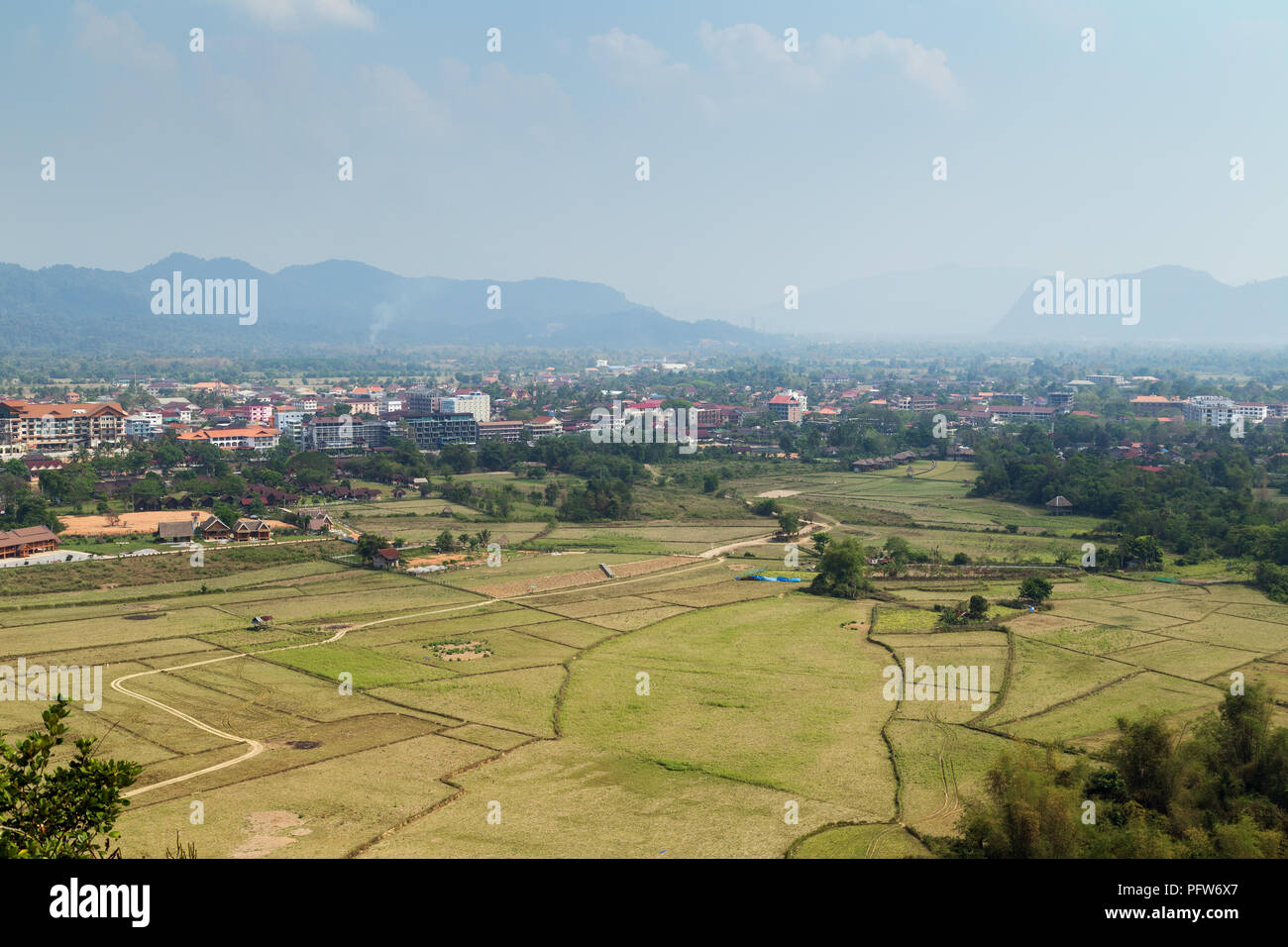 Beautiful view of town and fields from above in Vang Vieng, Vientiane Province, Laos, on a sunny day. - Stock Image
