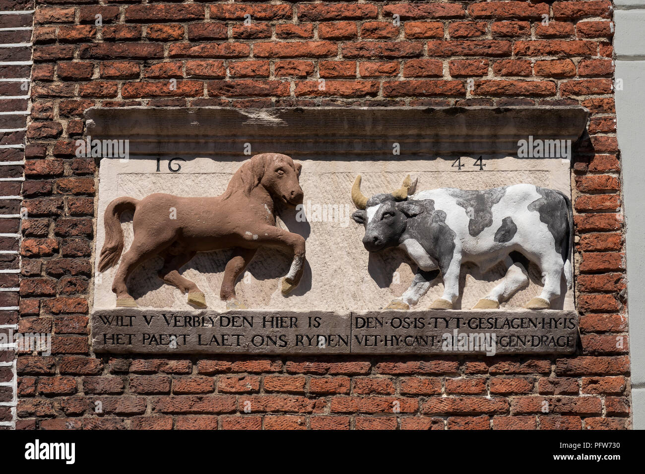 Leiden, Netherlands - August 3, 2018: Historical gable stone showing a horse and an ox, made in 1644 on a facade above a gate at the Stllle Rijn - Stock Image