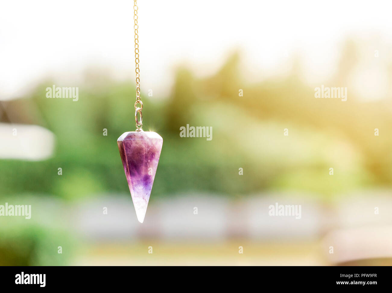 Violet natural Amethyst crystal pendulum hanging on chain on green outdoors nature background. - Stock Image
