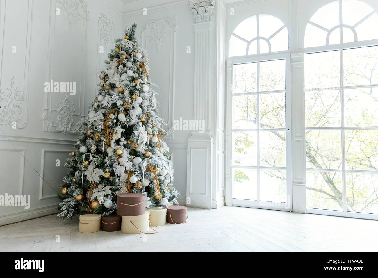 classic christmas and new year decorated interior room with presents and new year tree christmas tree with white and gold decorations - Classic Christmas Tree Decorations
