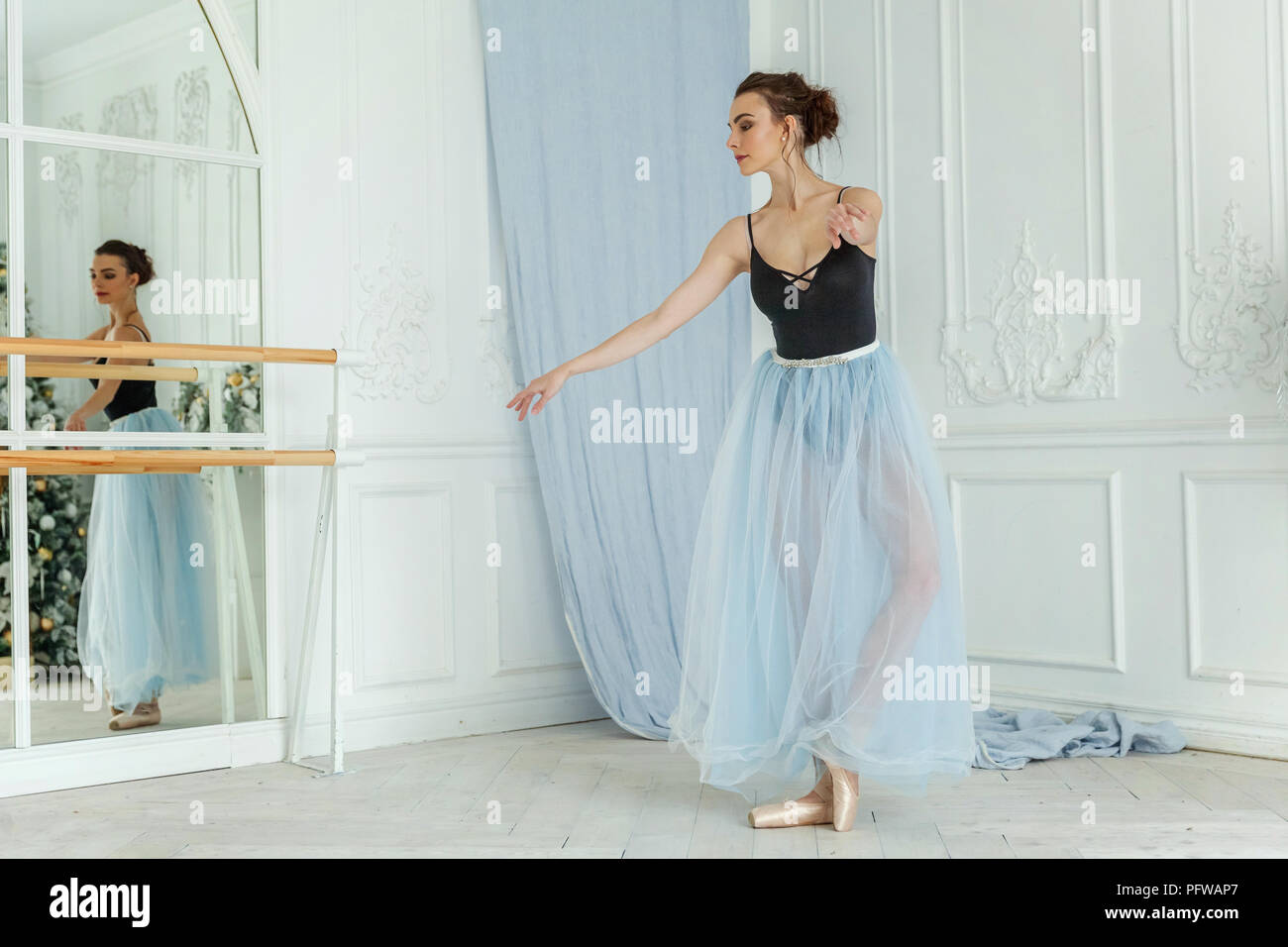 Young classical Ballet dancer side view. Beautiful graceful ballerine practice ballet positions in tutu skirt near large mirror in white light hall. B - Stock Image