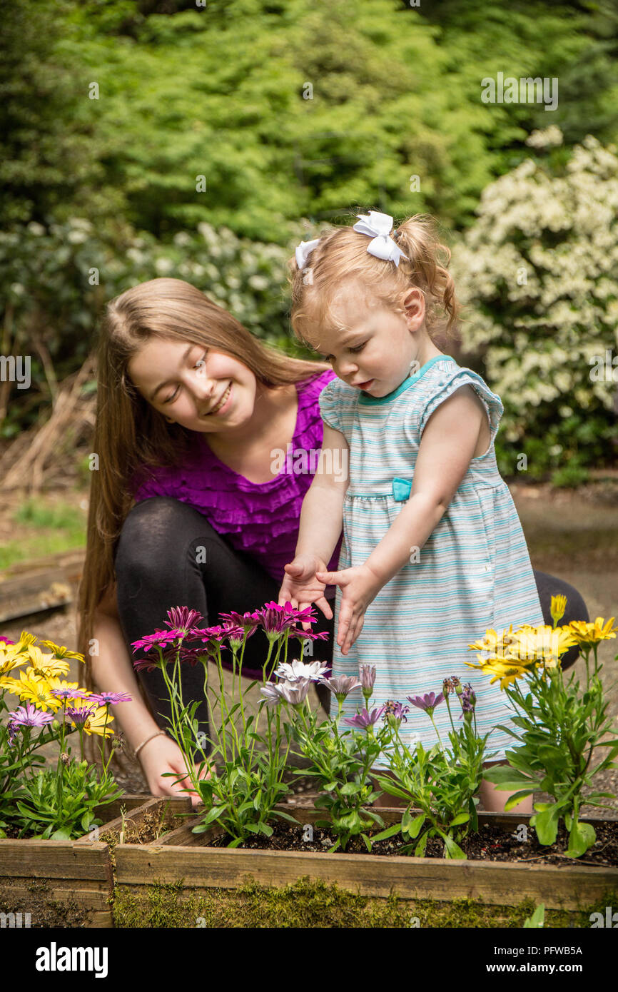 12 and 1 year old cousins admiring the flowers (MR) - Stock Image