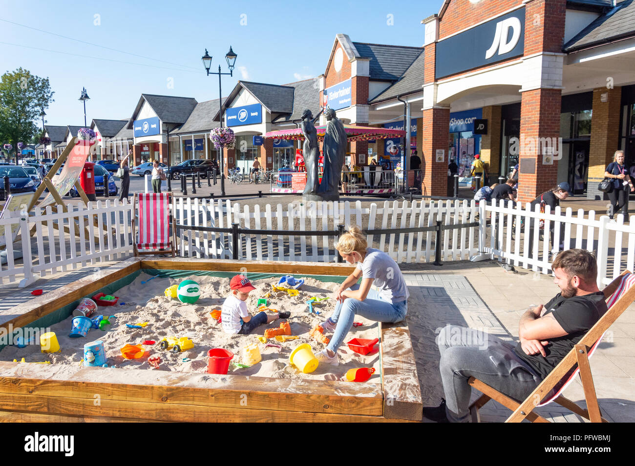 Family at children's sandpit, Two Rivers Shopping Centre, Staines-upon-Thames, Surrey, England, United Kingdom - Stock Image