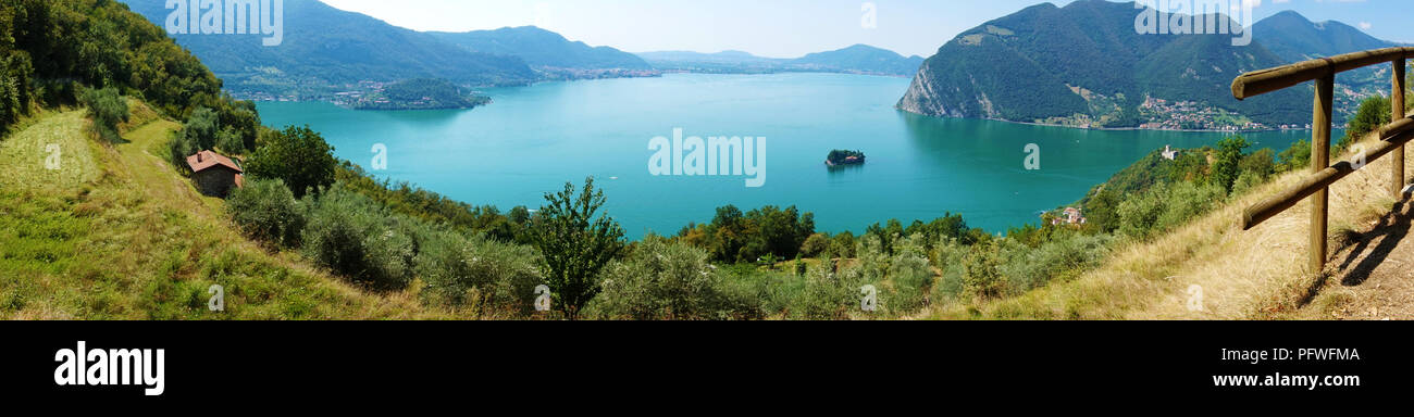 Panoramic view of mountain lake with island in the middle. Panorama from Monte Isola Island with Lake Iseo, Italy. Italian landscape. Island on lake. - Stock Image