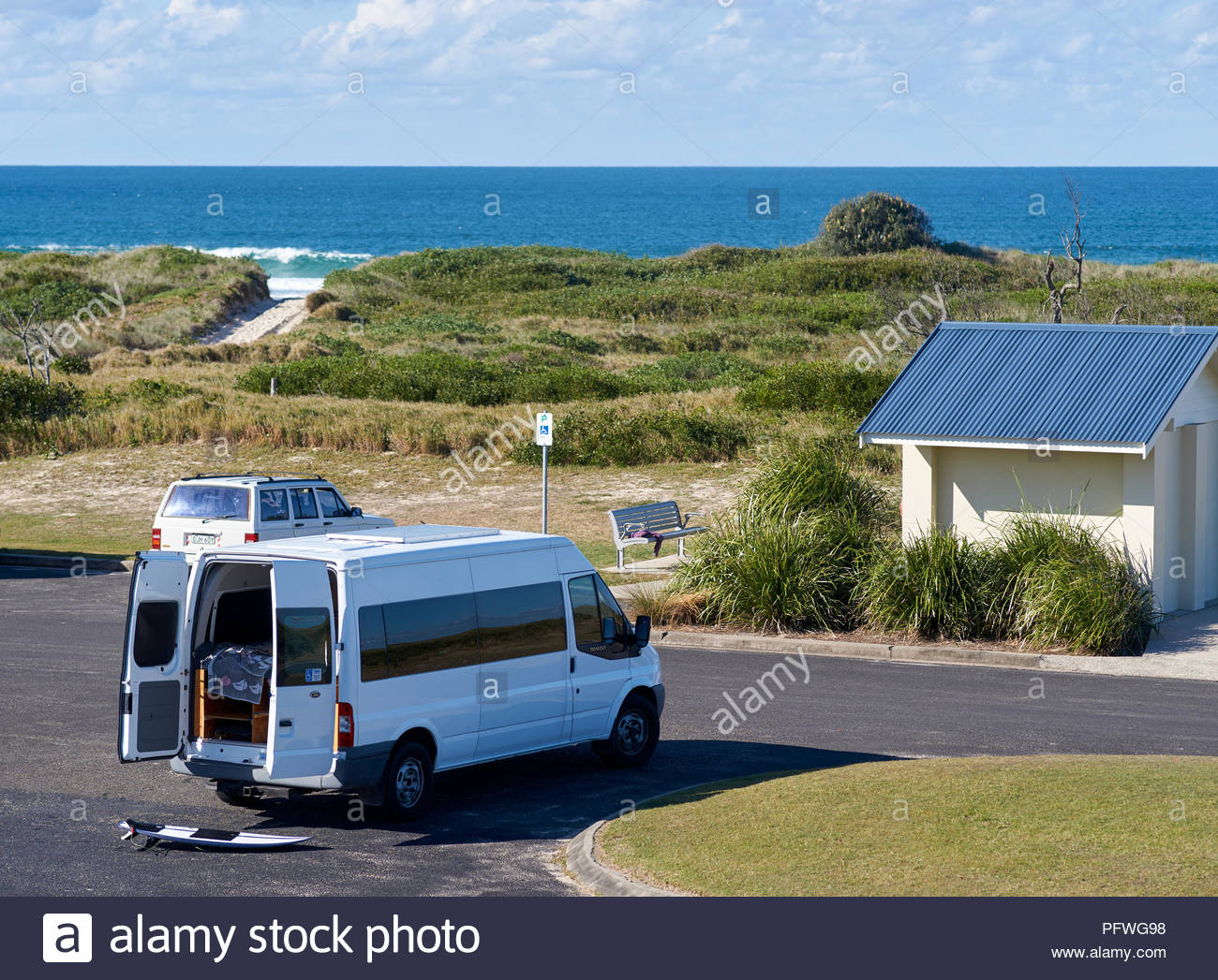 A white camper van, parked at the beach, with the back doors open and a surfboard lying on the ground. Taken at the North Wall, Iluka, NSW, Australia. - Stock Image