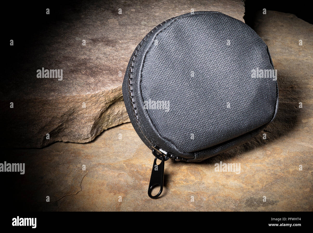 Black zippered tactical cleaning pouch on two rocks - Stock Image