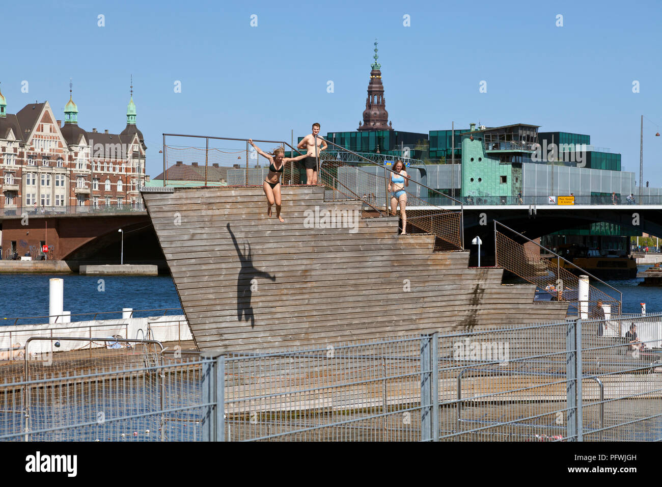 Girl jumping from the diving tower of Islands Brygge Harbour Bath in the inner harbour in central Copenhagen, Denmark on a sunny and warm summer's day Stock Photo