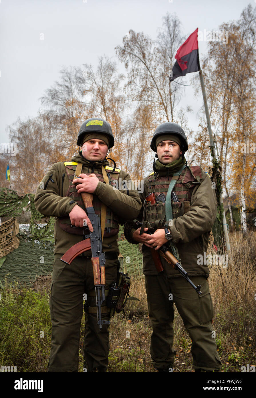 Soldiers in the Ukrainian Army at a checkpoint in eastern Ukraine, in front of the UPA (Ukranian Insurgent Army) flag. - Stock Image