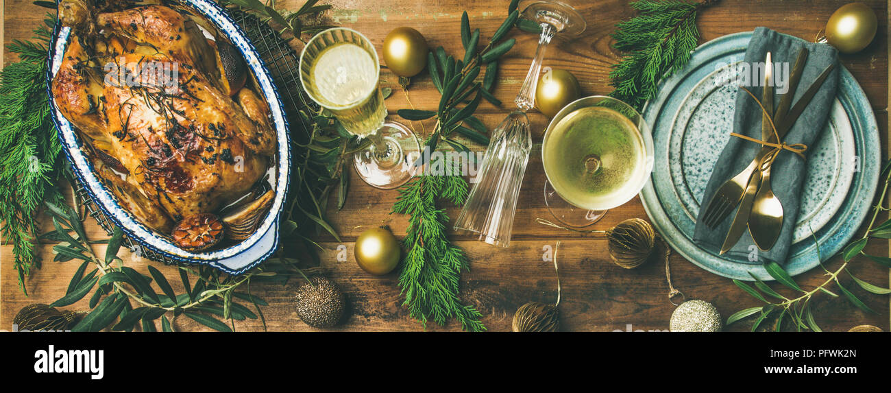 Holiday celebration table setting over rustic wooden background, wide composition - Stock Image