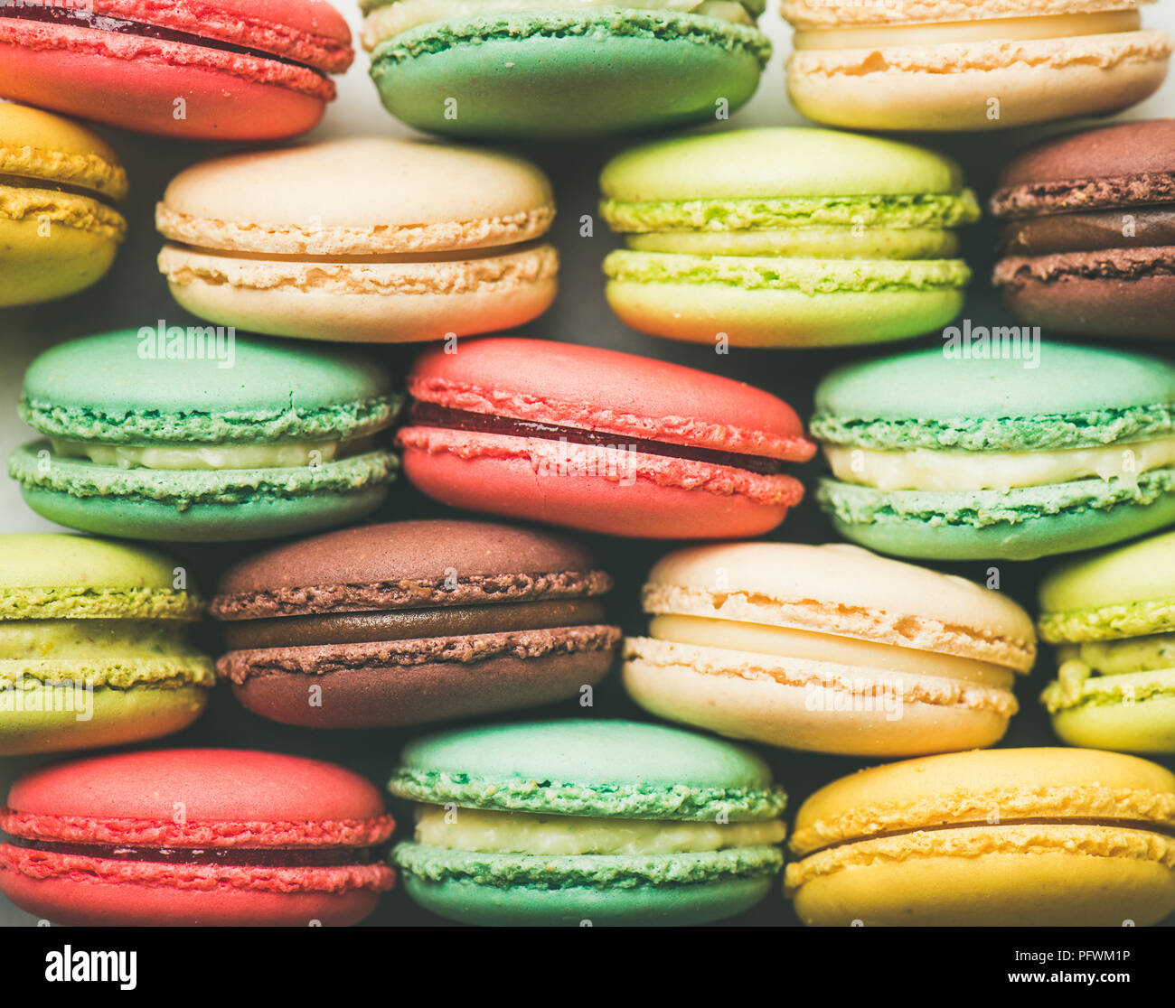 Colorful French macaroons cookies stacked in rows - Stock Image