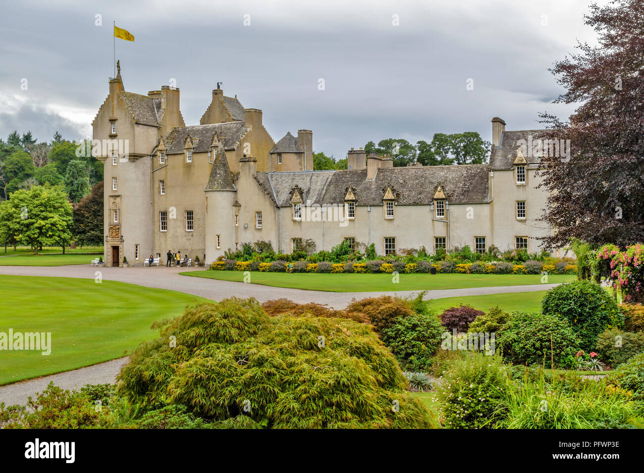 BALLINDALLOCH CASTLE SPEYSIDE SCOTLAND TOURISTS NEAR THE ENTRANCE OF THE CASTLE  AND A GARDENER TENDING THE FLOWER BEDS - Stock Image