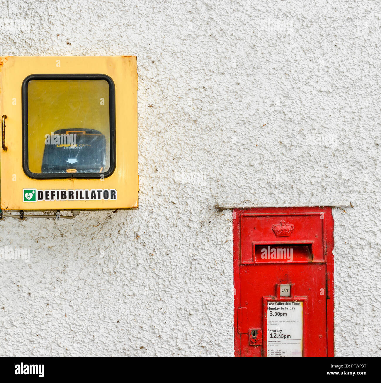 DEFIBRILLATOR AND RED LETTER BOX ON A WHITE WALL - Stock Image