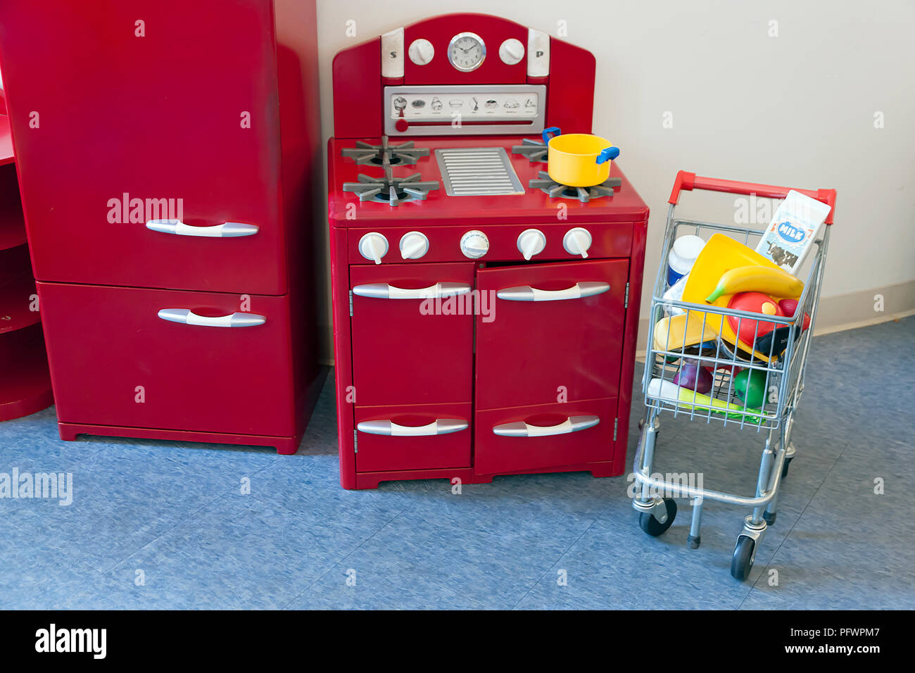 Cooktop stove, oven, refrigerator and shopping cart toys for children. - Stock Image