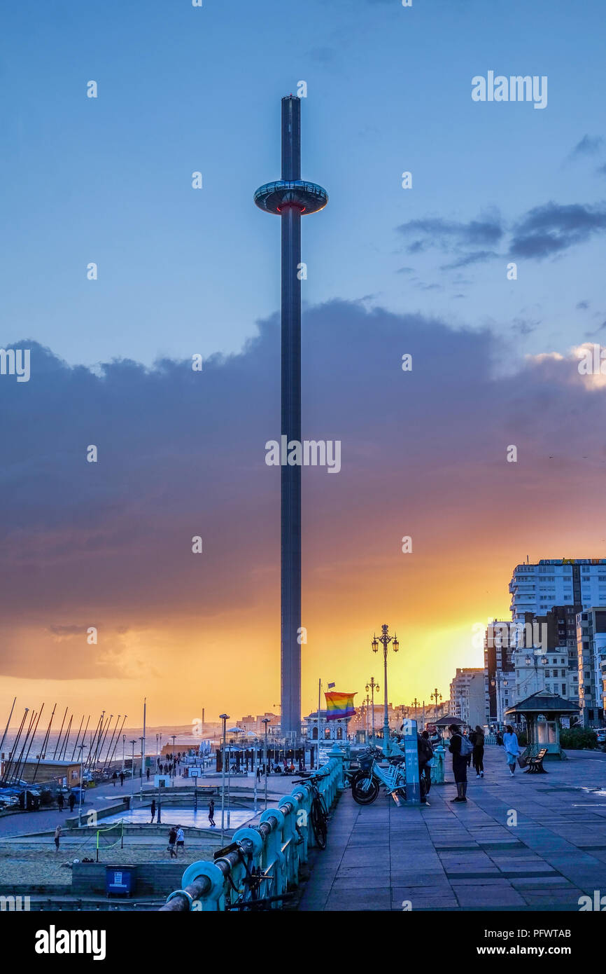 Brighton promenade at sunset with the moving viewing tower in the centre the promenade is very busy a pride flag is flying in the background the sky i - Stock Image