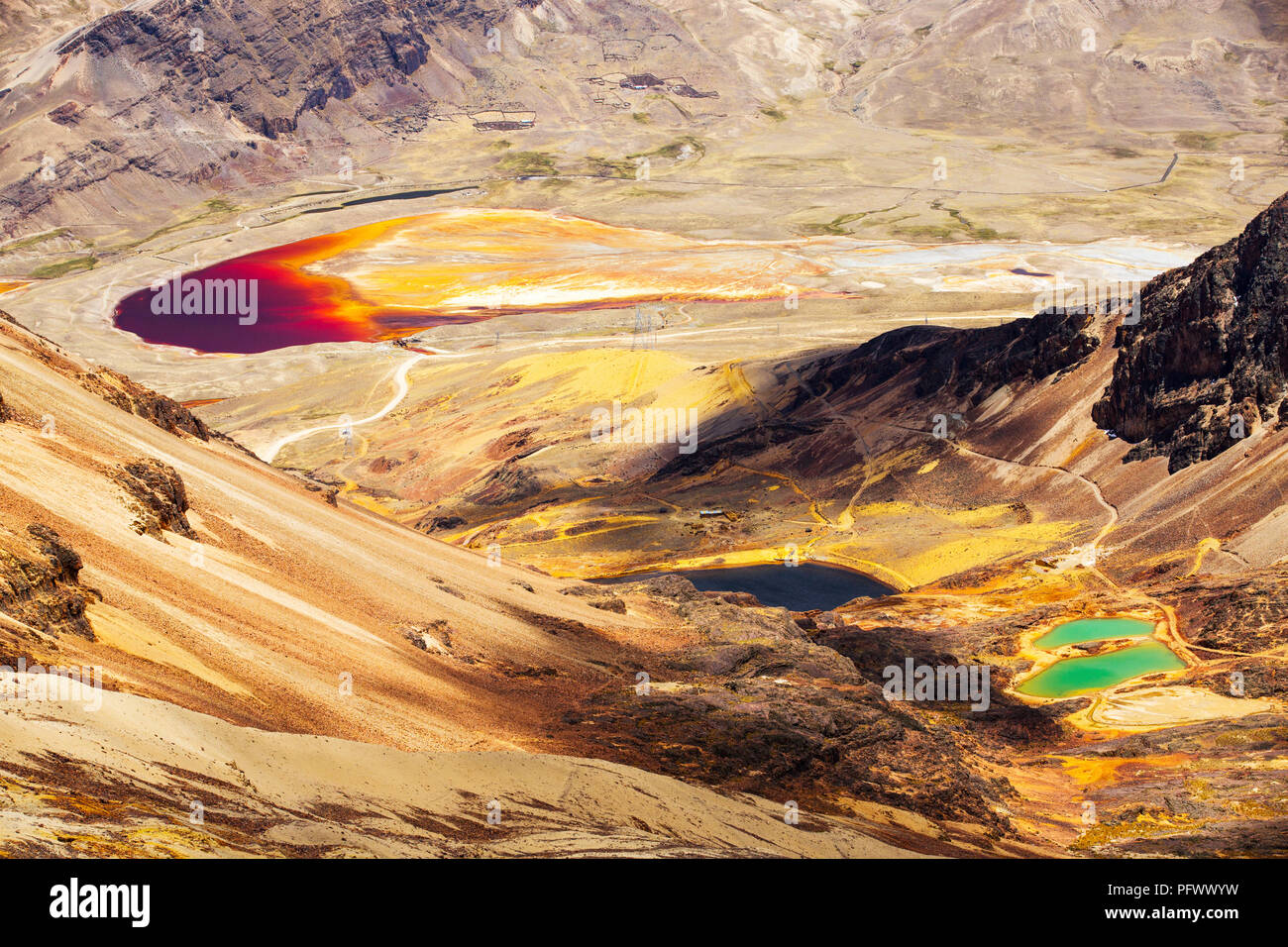 Colourful lakes below the peak of Chacaltaya in the Bolivian Andes, with a lake discoloured by mine effluent. - Stock Image