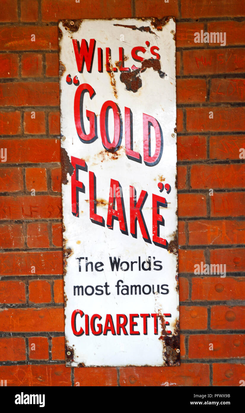An old enamel sign advertising Will's Gold Flake Cigarettes at the railway station at Acle, Norfolk, England, United Kingdom, Europe. - Stock Image