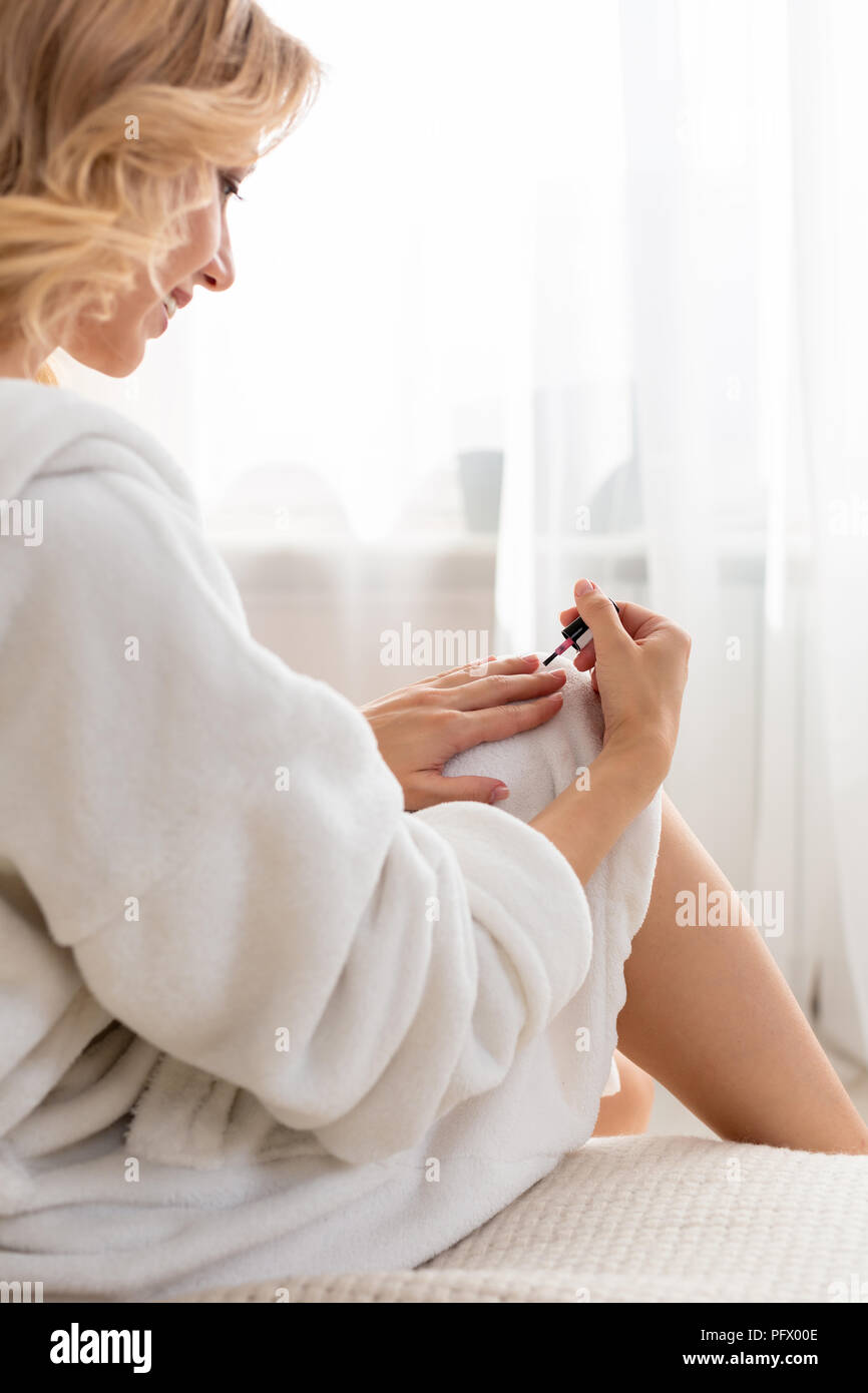 Close up of a shapely woman painted her nails in the morning, while sitting on the bed being dressed in a dressing-gown. - Stock Image