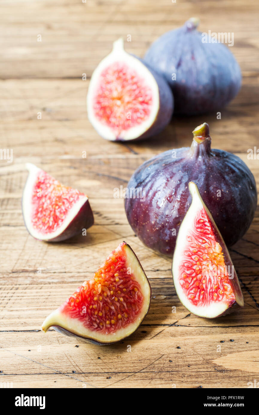 Figs are Fresh ripe whole and cut into a wooden old background - Stock Image