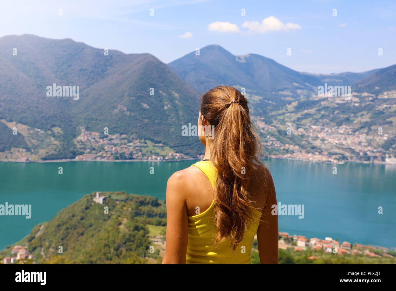 Young woman hiker standing admiring a mountaintop view looking out over distant ranges of mountains and valleys in a healthy active lifestyle concept - Stock Image