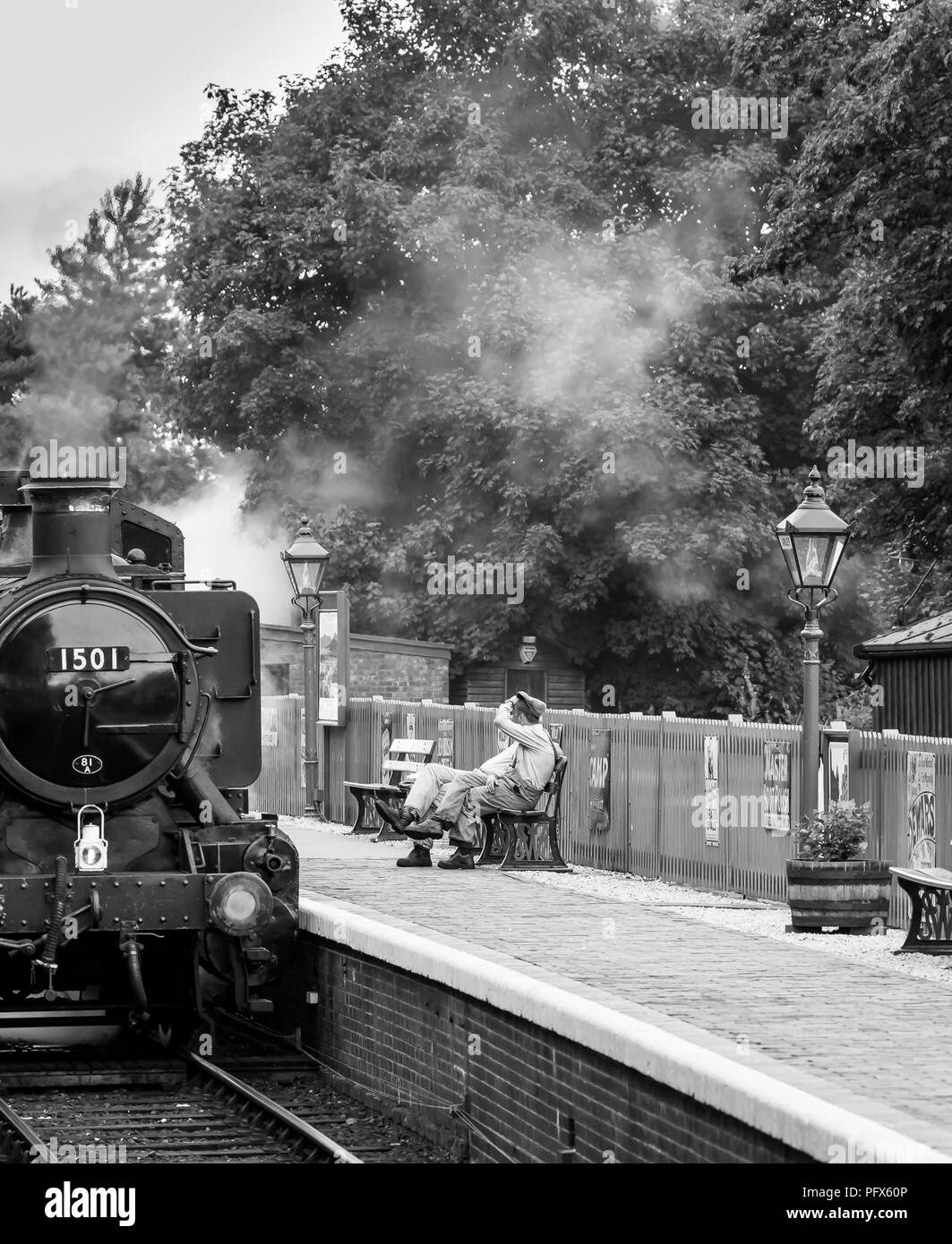 Black & white shot of steam engine crew taking a quick break outside the cab, Severn Valley Railway's Arley station. Front view of loco 1501 steaming. - Stock Image