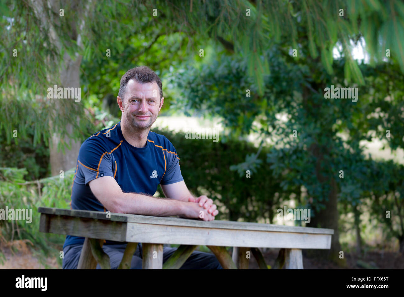 Man in close-fitting T-shirt sat alone at a picnic table in outside rural setting looking face-on to camera, waiting for his lunch. Service is slow! - Stock Image