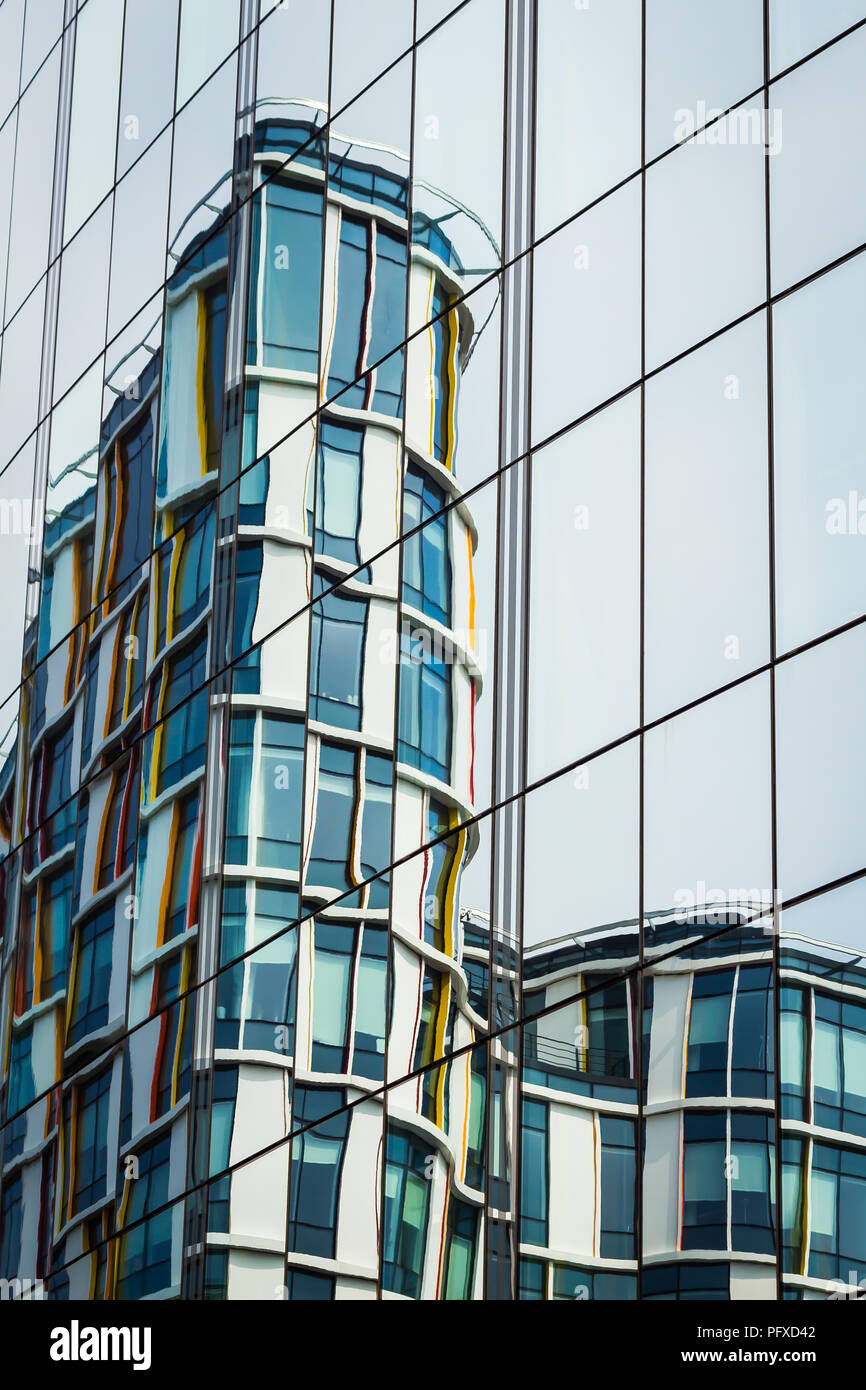 a modern building reflects in a glass wall of an office centre - Stock Image