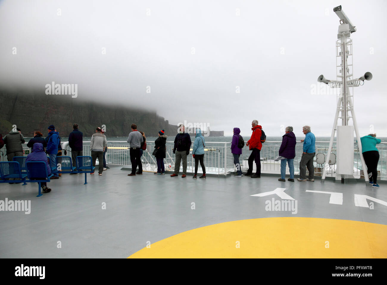 Passengers on the Northlink ferry from Scrabster to Stromness with the Old Man of Hoy, Orkney in the background - Stock Image