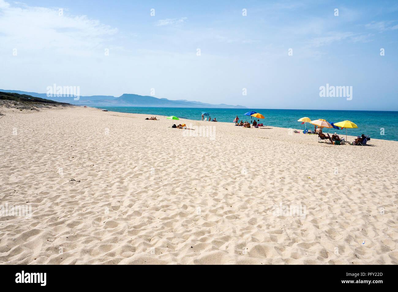 White sand beach with colorful umbrellas and bathers, Badesi, Sassari province, Sardinia, Italy - Stock Image