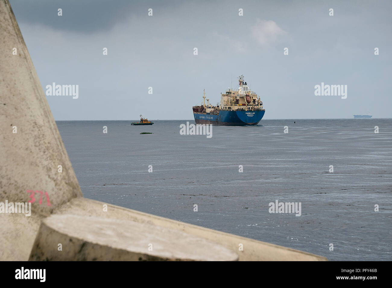 COATZACOALCOS, VER/MEXICO - AUG 18, 2018:  Maritime pilot guiding the Caribe Ilse Oil & Chemical tanker, at the river  mouth, a tetrapod in foreground - Stock Image