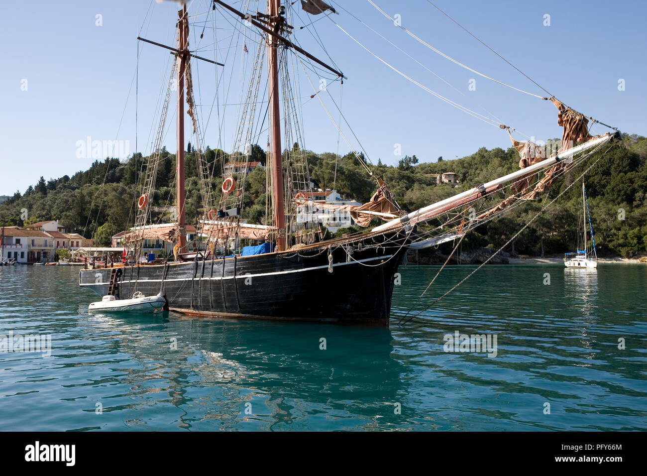 The harbour at Lakka, Paxos, Greece in early morning, with the topsail schooner Rhea at anchor - Stock Image