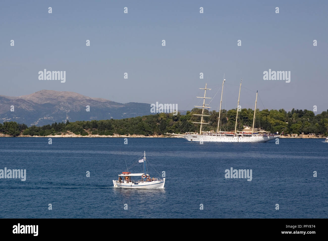 The island of Vido from Arseniou in Corfu Town, with the 'Star Clipper', a luxury cruise ship, rigged as a barquentine, entering Corfu harbour, Greece - Stock Image