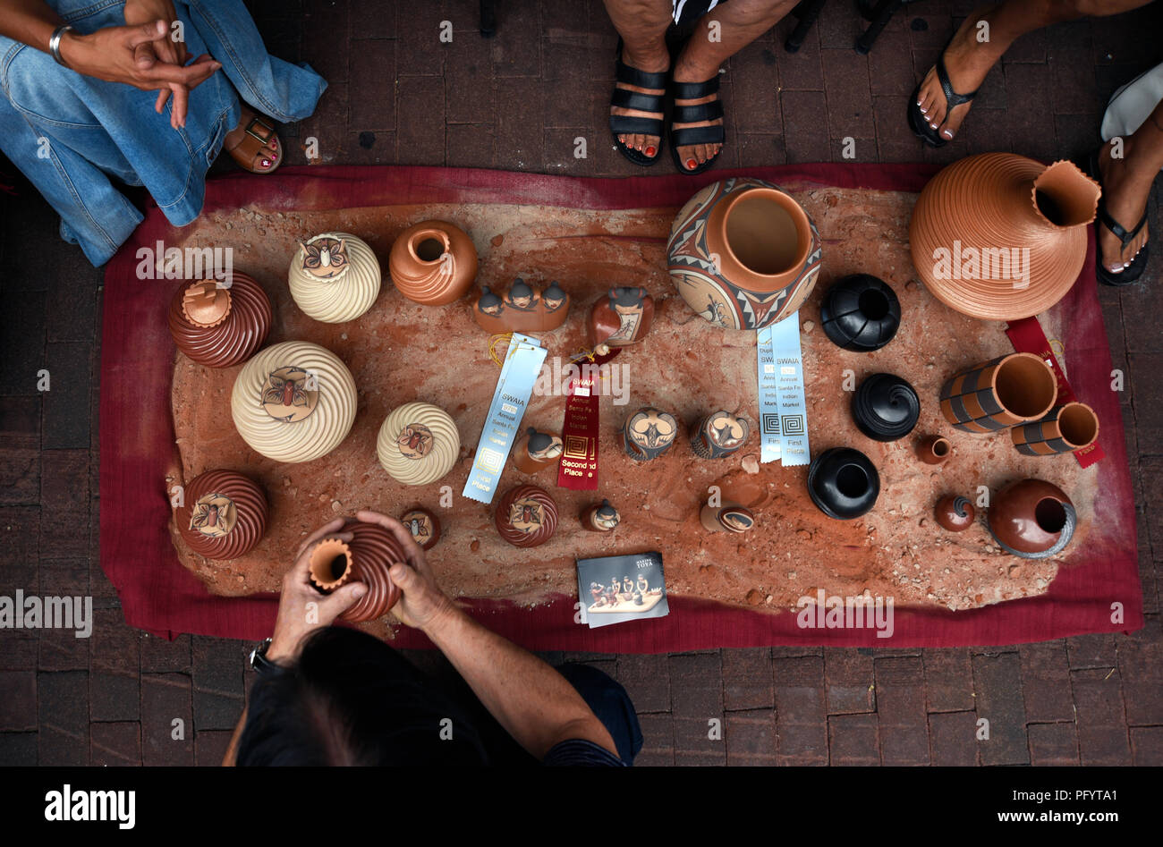 Native-American artists display and sell their clay pottery  at the Santa Fe Indian Market. - Stock Image