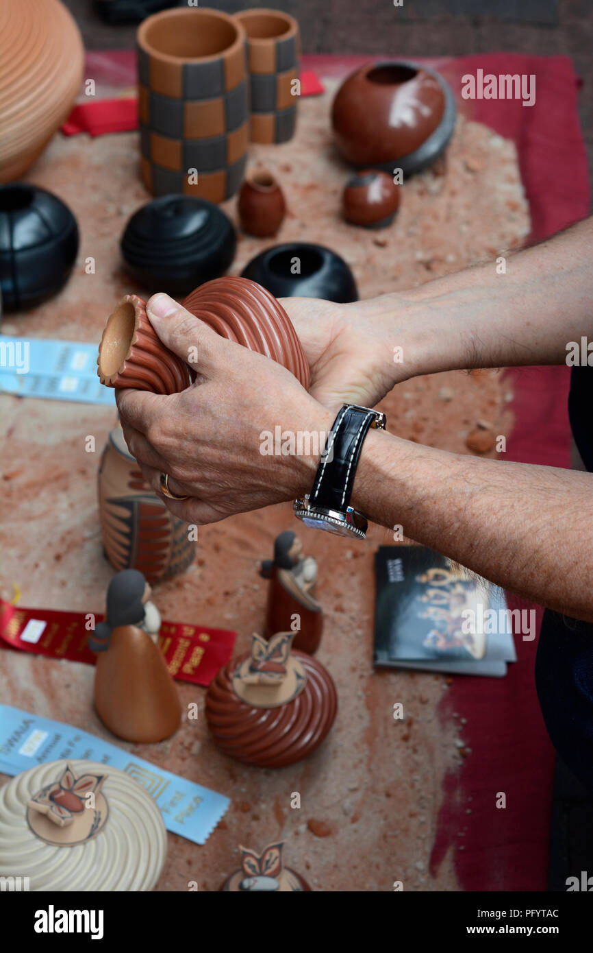 A customer inspects a Native-American clay vessel for sale at the Santa Fe Indian Market. - Stock Image