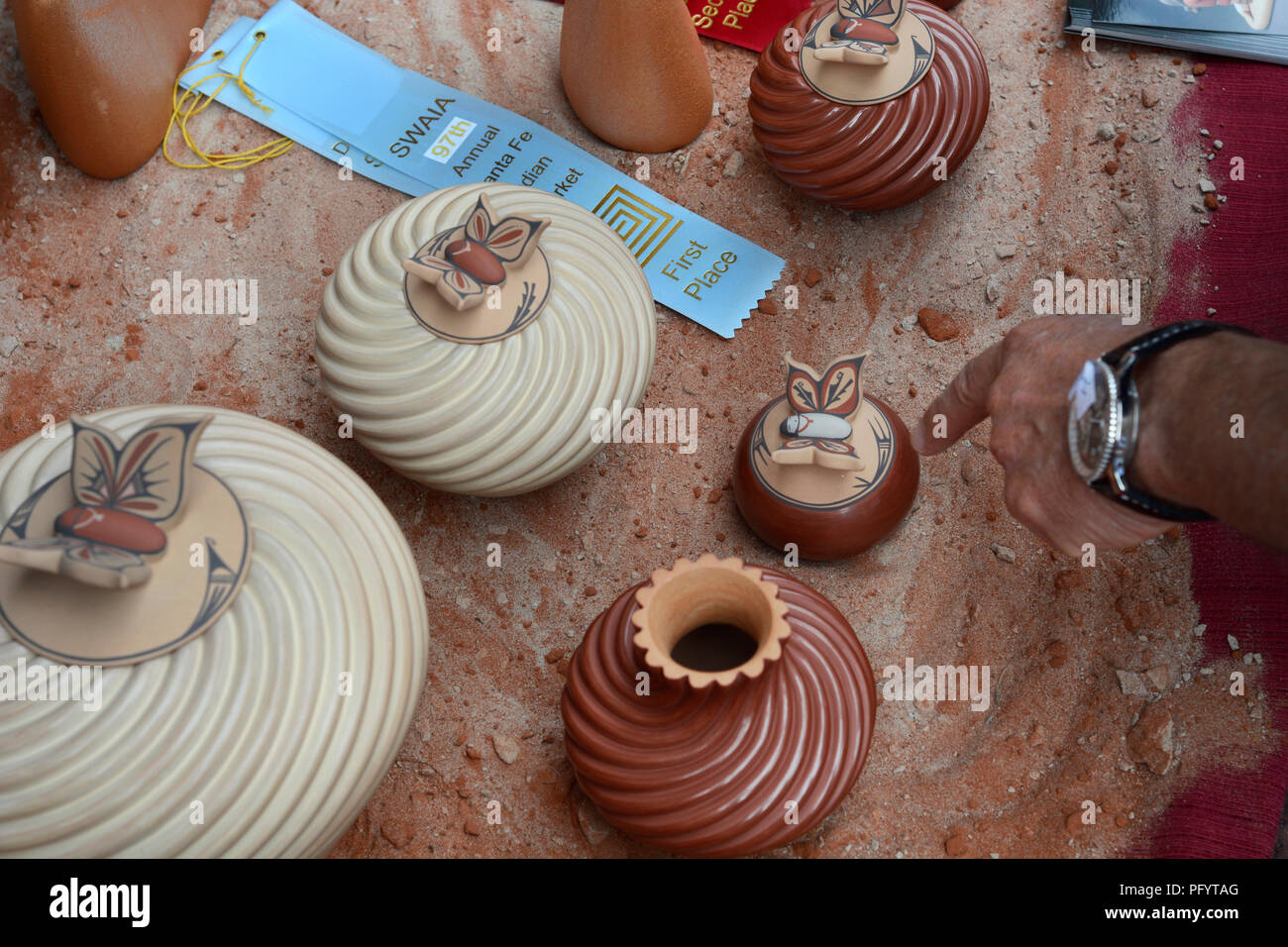 A customer points toward a Native-American clay vessel for sale at the Santa Fe Indian Market. - Stock Image