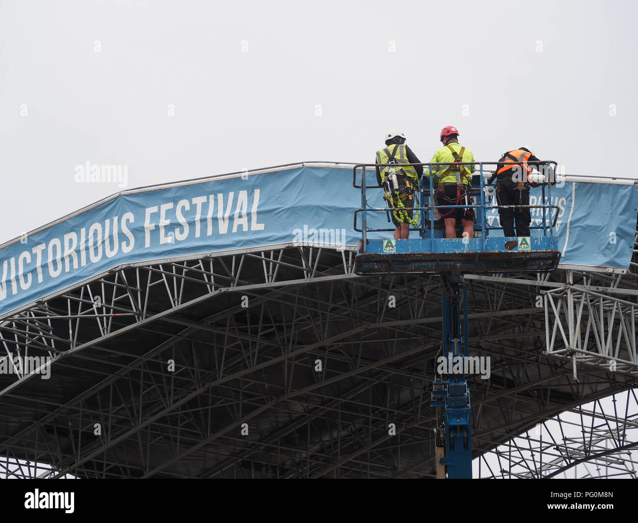 Three workers in a cherry picker assisting in the huilding of a stage for a music festival - Stock Image