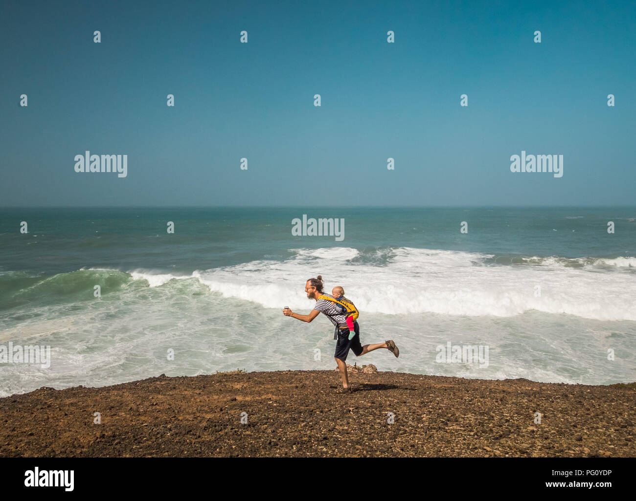 Father with his baby on back goofing around at seaside. - Stock Image