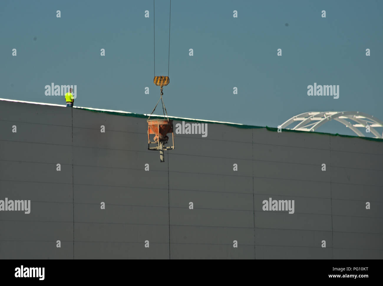 NOVI SAD, SERBIA - July 14th: Worker supervising crane lifting weight - Stock Image