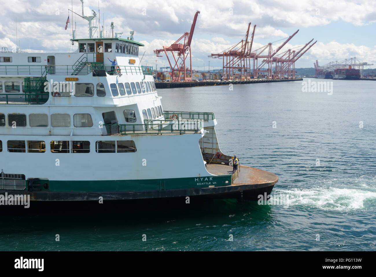 Washington State ferry boat leaving the Seattle Terminal with the cranes of the Seattle harbor in the background, USA. - Stock Image