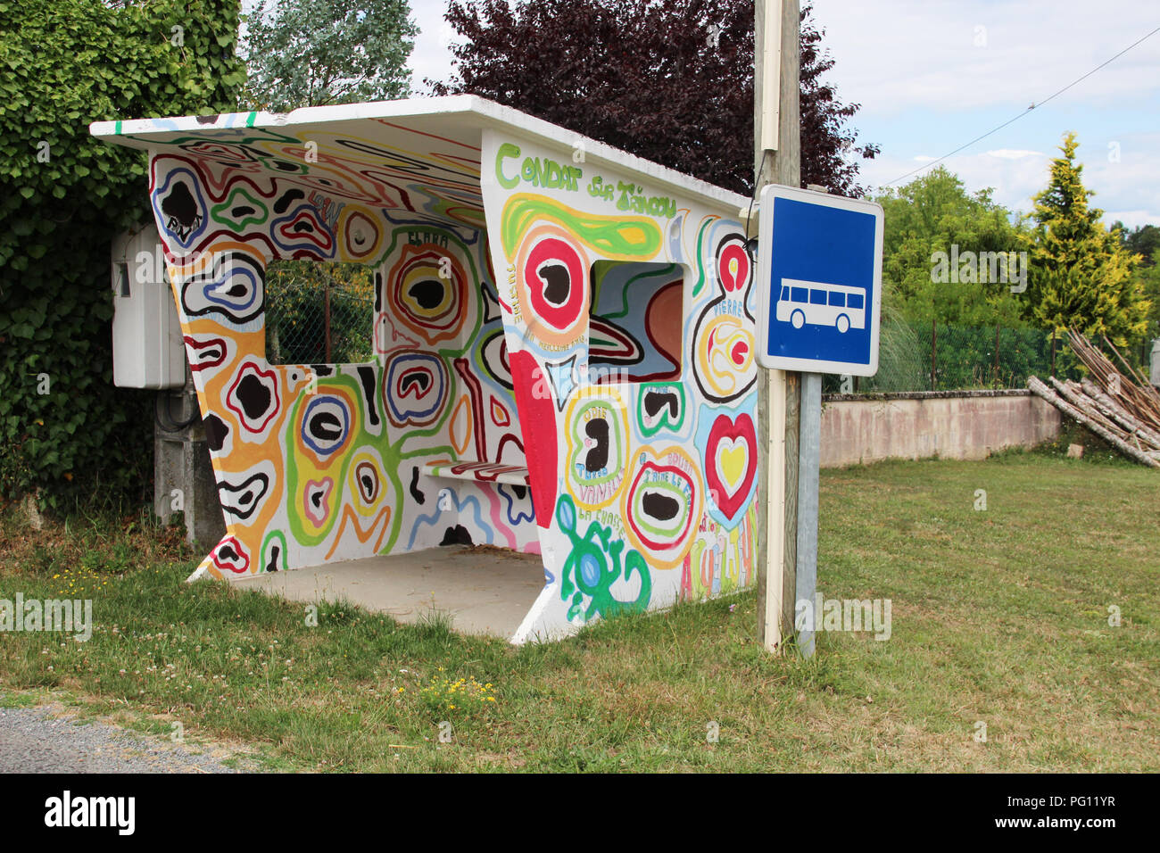 Country bus shelter hand painted in pyschedelic graffiti by local schoolchildren in village in France - Stock Image