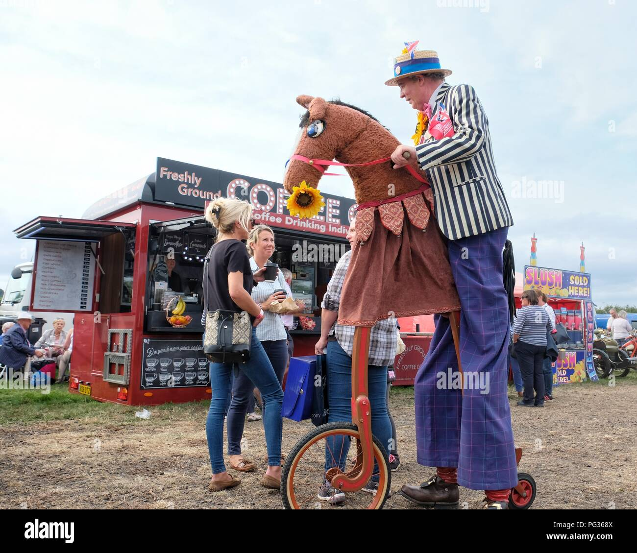 Melplash Agricultural Show, Bridport, Dorset, UK. 23 August 2018. Visitors enjoy one of the performance artists at the Melplash Agricultural Show in Bridport, Dorset.The one day agricultural show is a showcase and celebration for local farmers, producers, growers and craftspeople and is the South West's premier agricultural exhibition. Credit Tom Corban/Alamy Live News. - Stock Image