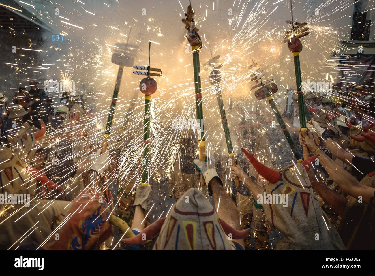 Sitges, Spain. 24 August, 2018:  Members of 'Diables de Sitges - Colla Vella' enlighten their fireworks among the crowd of spectators at the 'Festa Major de Sitges'. Credit: Matthias Oesterle/Alamy Live News - Stock Image